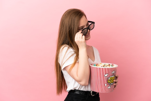 Teenager girl over isolated pink background with 3d glasses and holding a big bucket of popcorns