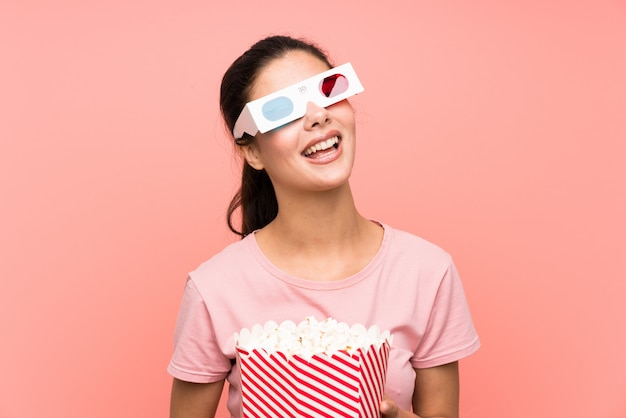 Teenager girl over isolated pink wall eating popcorns with 3d glasses