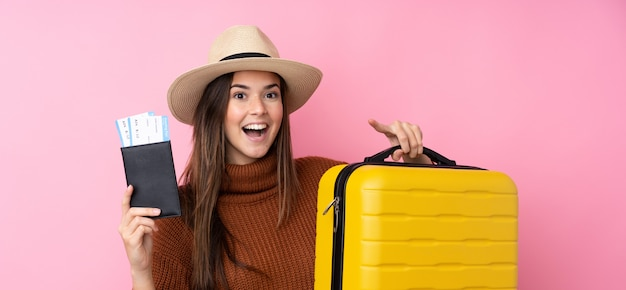 Teenager girl over isolated pink wall in vacation with suitcase and passport and surprised