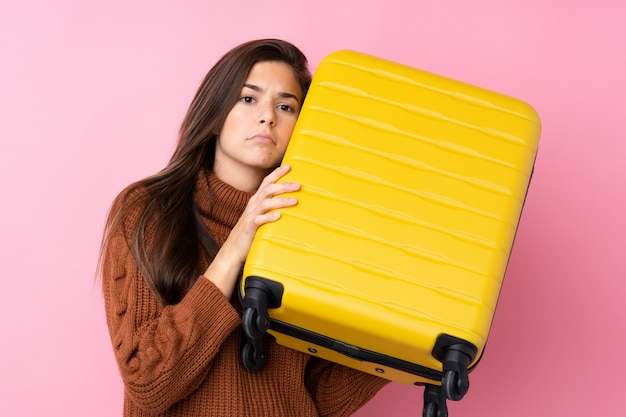 Teenager girl over isolated pink wall in vacation with travel suitcase and unhappy