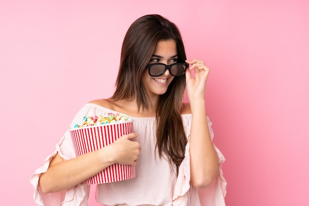 Teenager girl over isolated pink wall with 3d glasses and holding a big bucket of popcorns