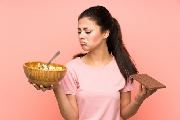 Teenager girl  over isolated pink wall with salad and chocolat and having doubts