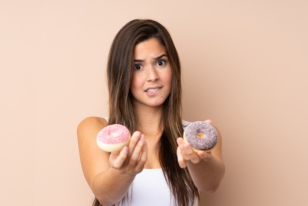 Teenager girl over isolated wall holding a donut and sad