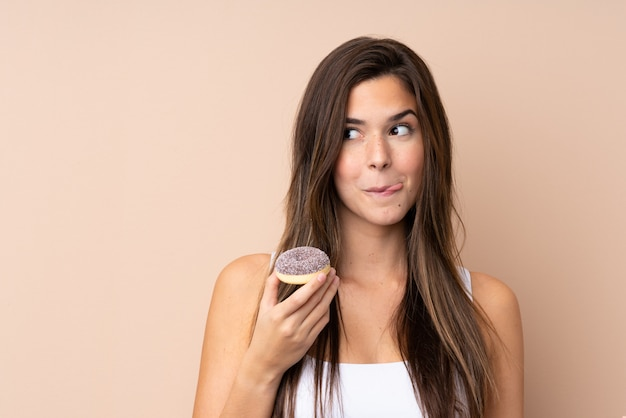 Teenager girl over isolated wall holding a donut