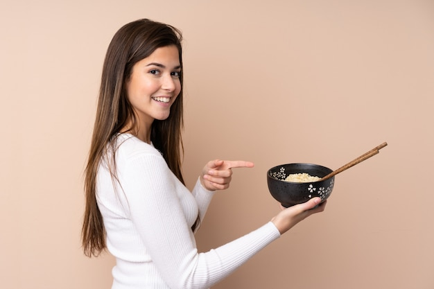 Teenager girl over isolated wall and pointing it while holding a bowl of noodles with chopsticks