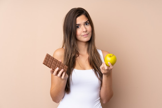 Teenager girl over isolated wall taking a chocolate tablet in one hand and an apple in the other