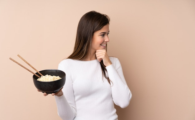 Teenager girl over isolated wall thinking an idea and looking side while holding a bowl of noodles with chopsticks