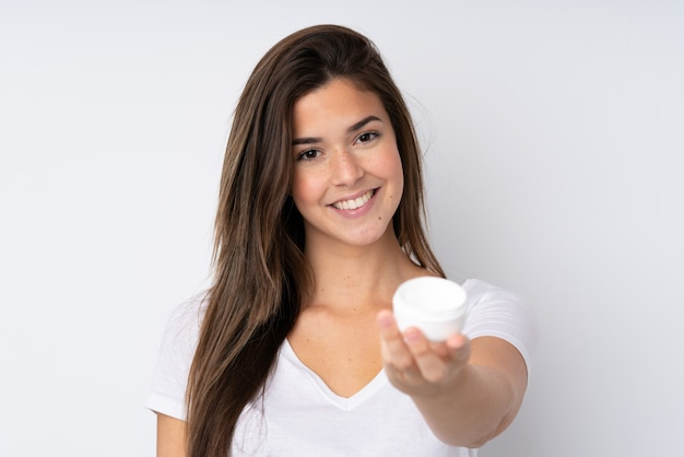 Teenager girl over isolated wall with moisturizer and offering it