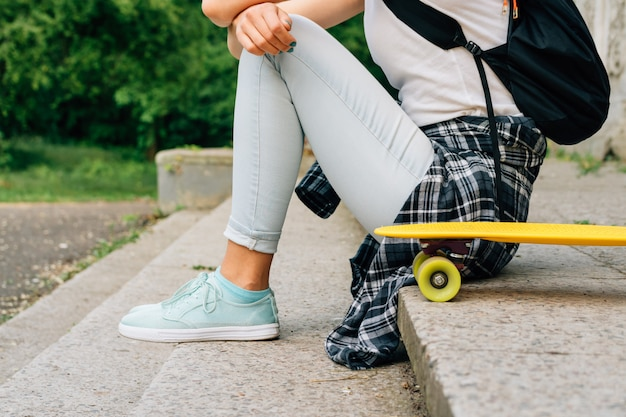 Teenager girl in jeans and a plaid shirt sitting on the steps near her skate outdoors