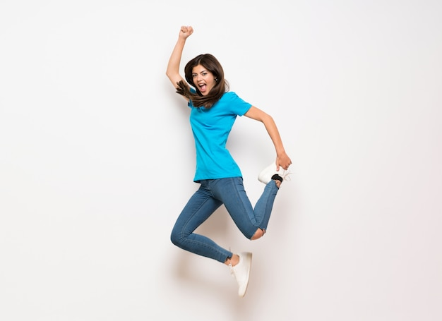 Teenager girl jumping over isolated white wall