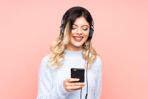音楽を聴いてモバイルを探しているティーンエイジャーの女の子