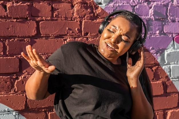 外のヘッドフォンを介して音楽を聴いている10代の女の子