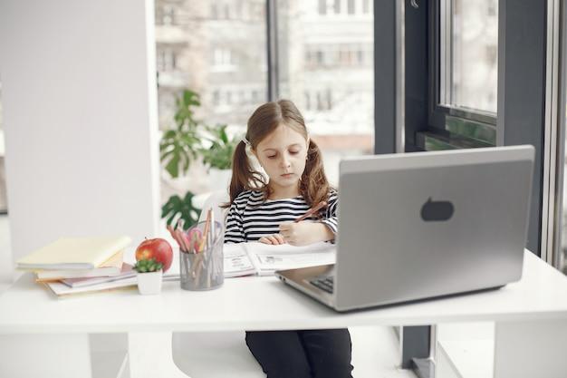 Ragazza dell'adolescente che esamina computer portatile. chiln al periodo di isolamento della quarantena durante la pandemia. istruzione domiciliare. riduzione dei contatti. test scolastico online.