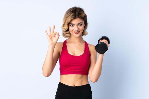 指でokの標識を示す重量挙げを作る10代の女の子