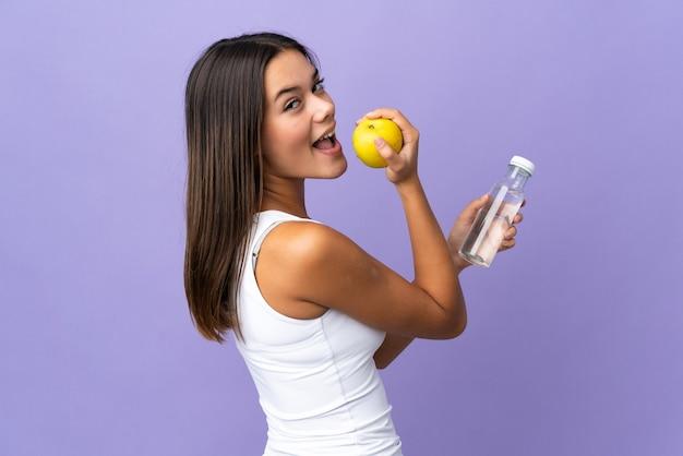 リンゴと水のボトルと紫のティーンエイジャーの女の子