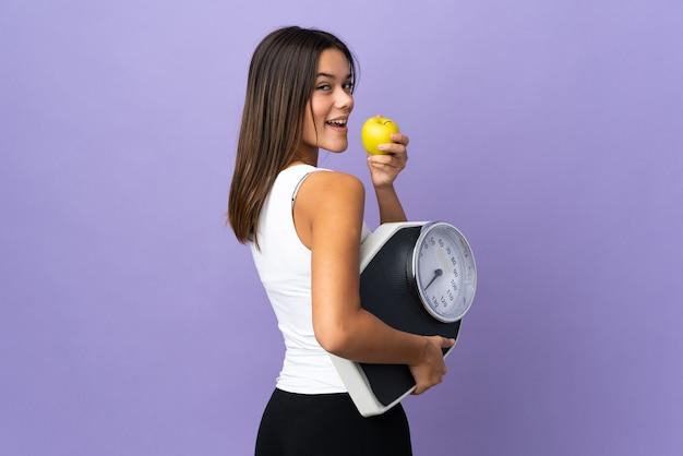 Девушка-подросток на фиолетовом с весами и с яблоком
