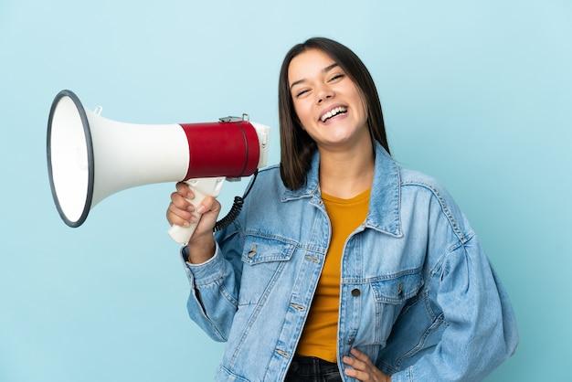 Девушка-подросток на желтом держит мегафон и улыбается
