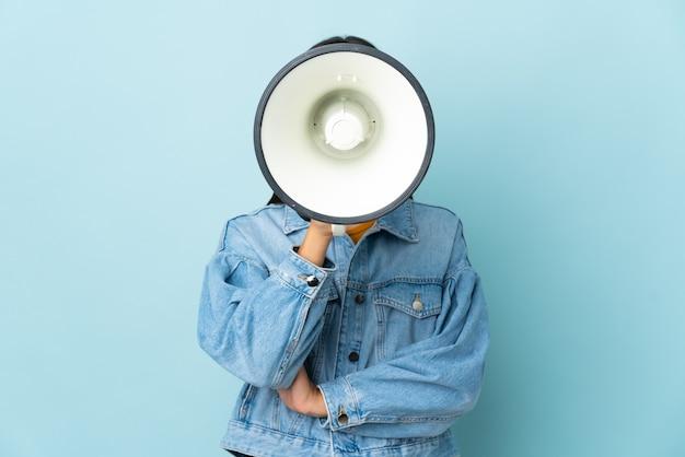 Девушка-подросток на желтом кричит в мегафон, чтобы что-то объявить