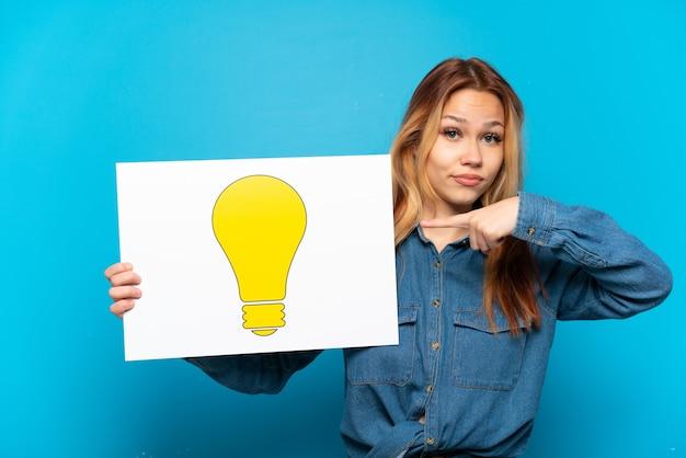 Девушка-подросток на изолированном синем фоне держит плакат со значком лампочки и указывает на него