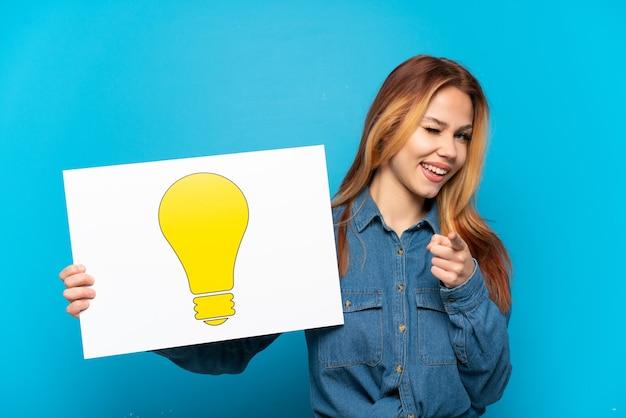電球のアイコンが付いたプラカードを保持し、正面を指している孤立した青い背景の上のティーンエイジャーの女の子