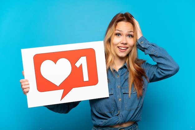 Девушка-подросток на изолированном синем фоне держит плакат со значком `` нравится '' с удивленным выражением лица
