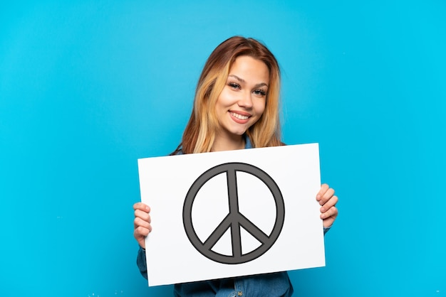 幸せな表情で平和のシンボルとプラカードを保持している孤立した青い背景の上のティーンエイジャーの女の子
