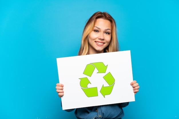 幸せな表情でリサイクルアイコンとプラカードを保持している孤立した青い背景の上のティーンエイジャーの女の子