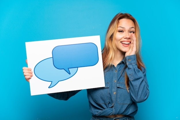 Девушка-подросток на изолированном синем фоне держит плакат со значком речевого пузыря и кричит