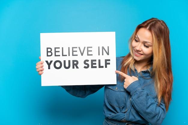 Девушка-подросток на изолированном синем фоне держит плакат с текстом «верь в себя» и указывает на него