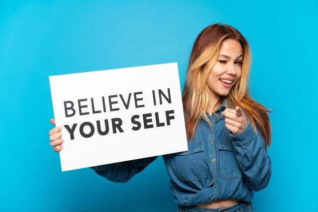 Девушка-подросток на изолированном синем фоне держит плакат с текстом «верь в себя» и указывает вперед