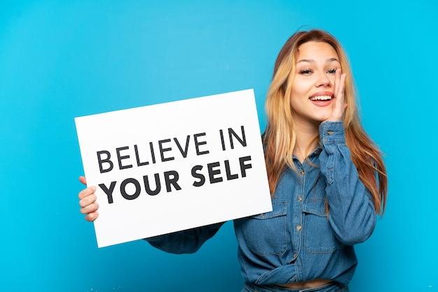 Девушка-подросток на изолированном синем фоне держит плакат с текстом «верь в себя» и кричит