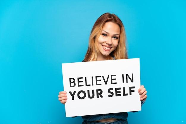 Девушка-подросток на изолированном синем фоне держит плакат с текстом верю в себя со счастливым выражением лица