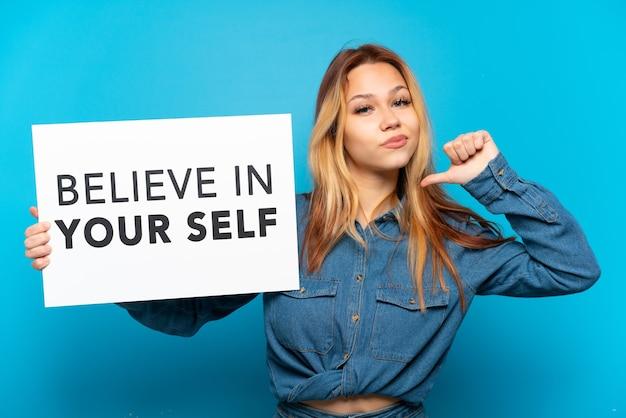 고립된 파란색 배경 위에 있는 10대 소녀가 자랑스러운 제스처로 자신을 믿으라는 문구가 적힌 플래카드를 들고 있습니다.
