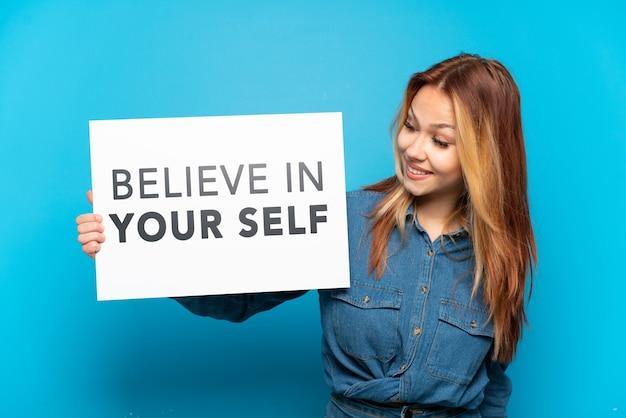 Девушка-подросток на изолированном синем фоне держит плакат с текстом верю в себя
