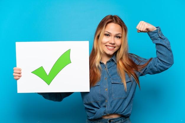 Девушка-подросток на изолированном синем фоне держит плакат с текстом зеленой галочки и делает сильный жест