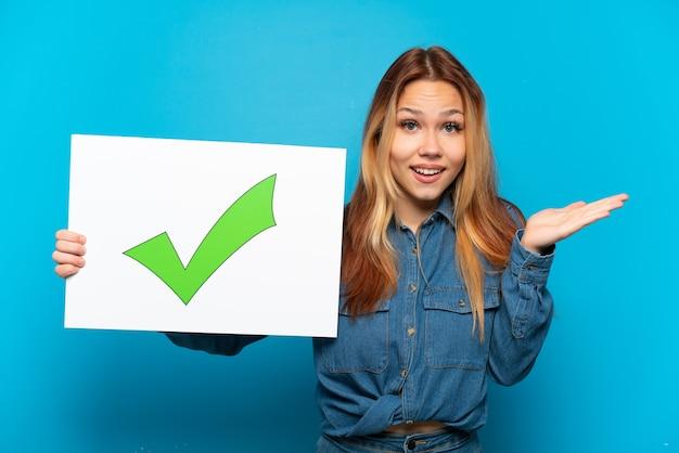 놀란 표정으로 텍스트 녹색 확인 표시 아이콘이 있는 플래카드를 들고 격리된 파란색 배경 위에 10대 소녀