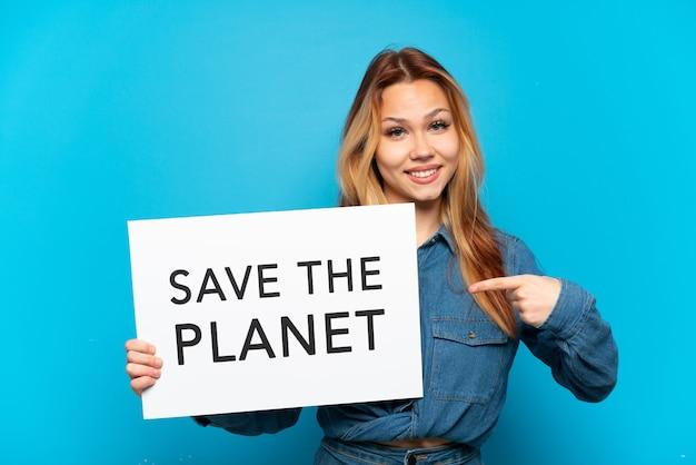 Девушка-подросток на изолированном синем фоне держит плакат с текстом «спасите планету» и указывает на него