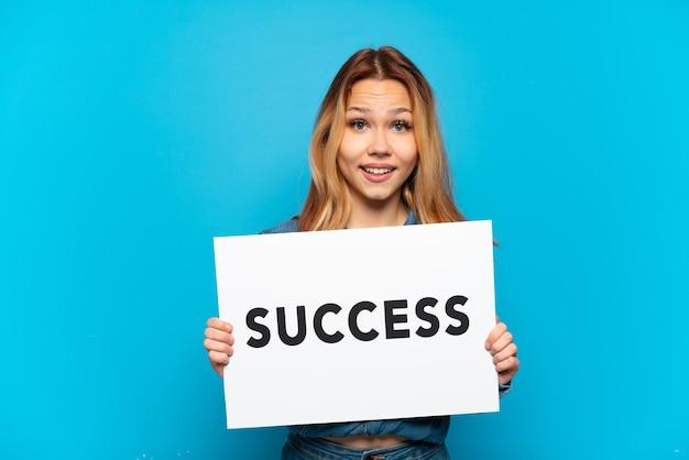 놀란 표정으로 success라는 문구가 적힌 플래카드를 들고 고립된 파란색 배경 위에 있는 10대 소녀
