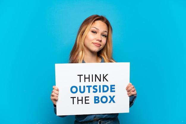 テキストのプラカードを保持している孤立した青い背景の上のティーンエイジャーの女の子は、ボックスの外側を考える