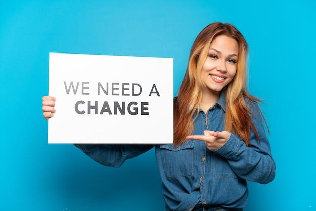Девушка-подросток на изолированном синем фоне держит плакат с текстом «нам нужны изменения» и указывает на него