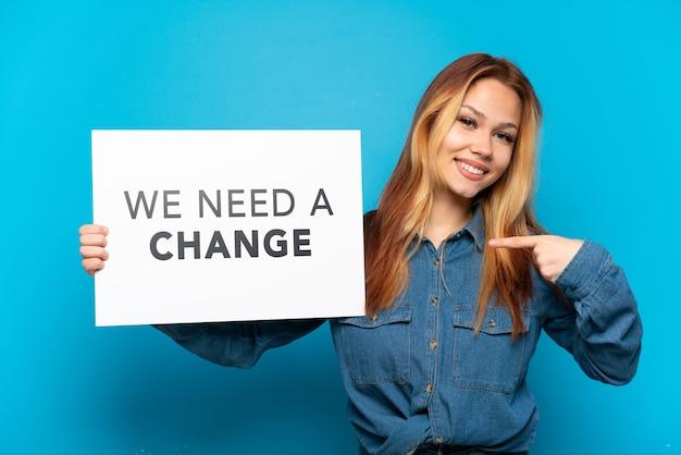 テキスト付きのプラカードを保持している孤立した青い背景の上のティーンエイジャーの女の子私たちは変更が必要です