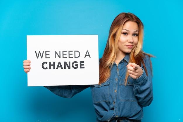 テキスト付きのプラカードを保持している孤立した青い背景の上のティーンエイジャーの女の子私たちは変更が必要であり、正面を指しています