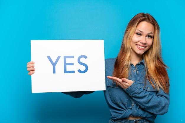 Девушка-подросток на изолированном синем фоне держит плакат с текстом да и указывает на него