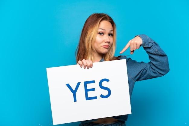격리된 파란색 배경 위에 있는 10대 소녀가 yes라는 문구가 적힌 플래카드를 들고 그것을 가리키고 있습니다.
