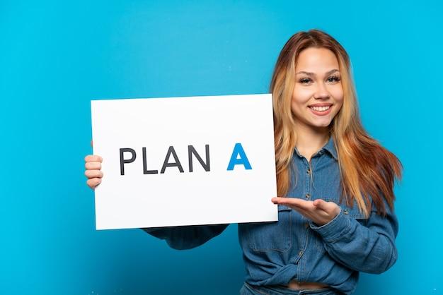 격리된 파란색 배경 위에 있는 10대 소녀가 plan a라는 메시지가 적힌 플래카드를 들고 그것을 가리키고 있습니다.