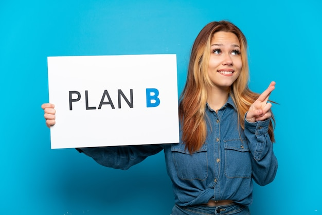 격리된 파란색 배경 위에 손가락이 교차하는 plan b라는 메시지가 있는 플래카드를 들고 있는 10대 소녀