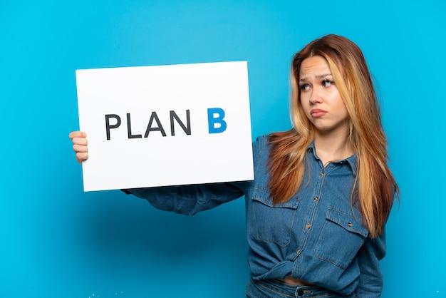 悲しい表情でメッセージプランbとプラカードを保持している孤立した青い背景の上のティーンエイジャーの女の子