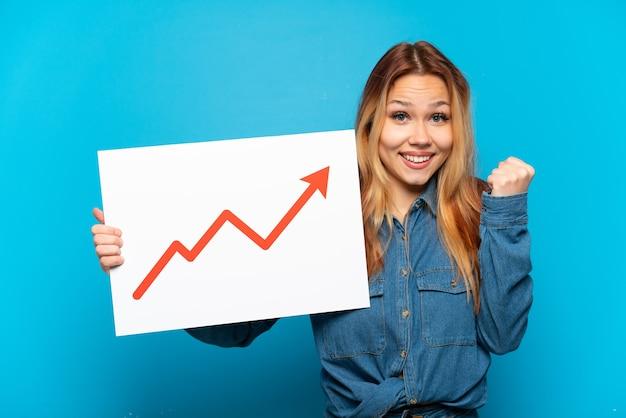 成長する統計矢印記号と勝利を祝う看板を保持している孤立した青い背景の上のティーンエイジャーの女の子
