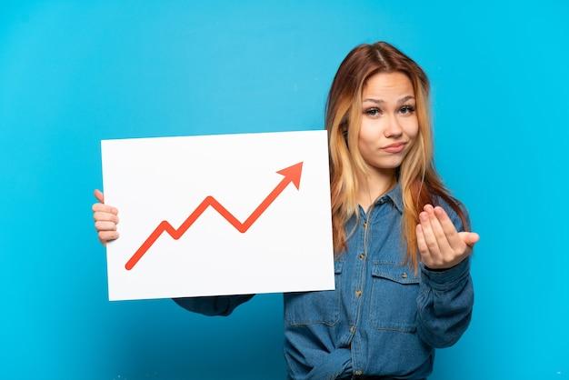 成長している統計矢印記号と次のジェスチャーをしている看板を保持している孤立した青い背景の上のティーンエイジャーの女の子