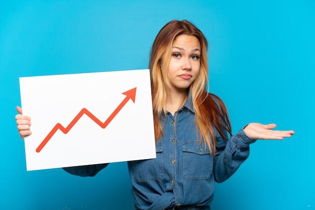 Девушка-подросток на изолированном синем фоне держит табличку с растущим символом стрелки статистики, имеющим сомнения